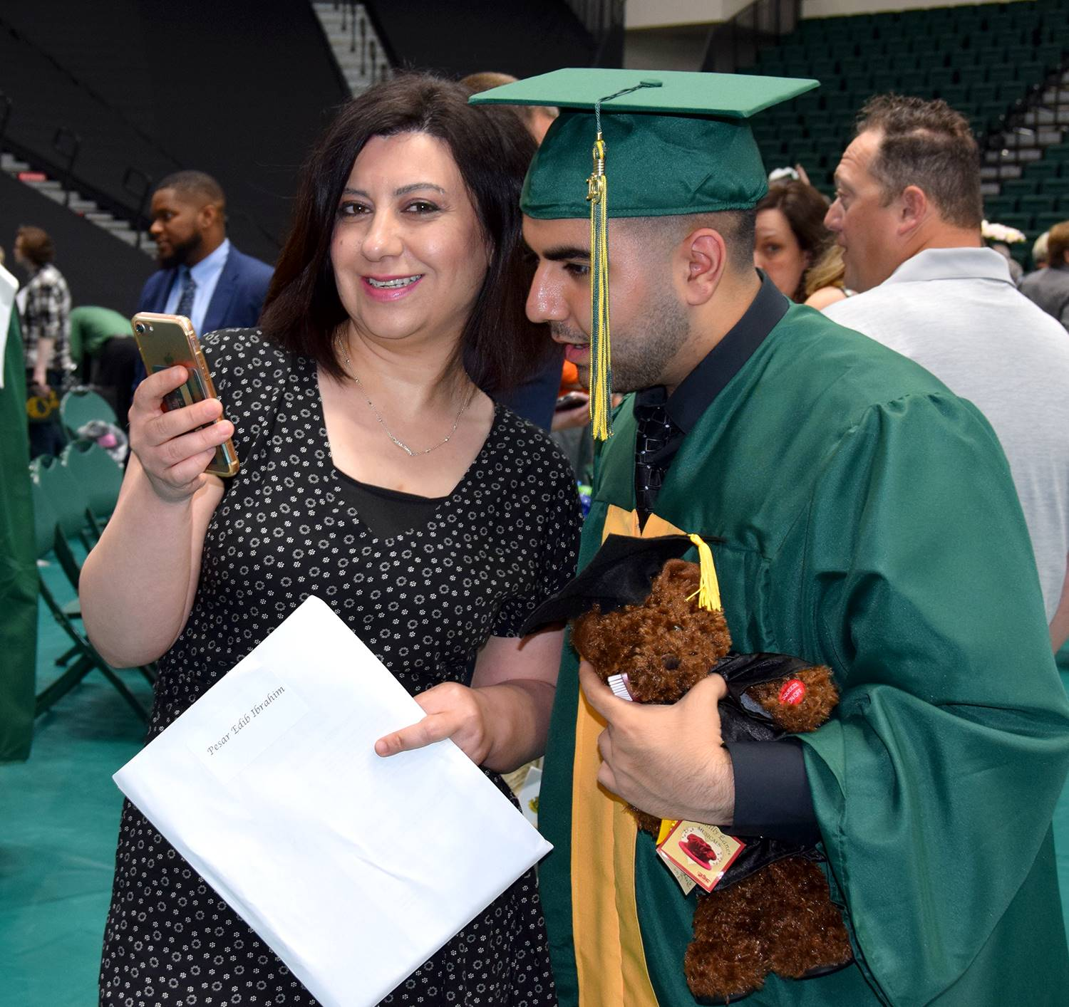 A Vestal High School graduate holding a small brown graduation bear looks over a female relative's s