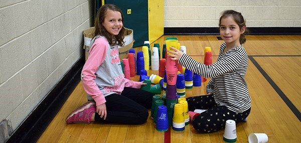 Two Vestal Hills Elementary girls stack cups during physical education class in the gym.