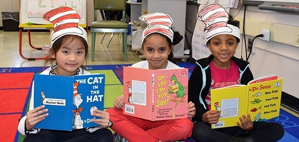 Three first-grade girls in red and white striped hats hold Dr. Seuss books in the Vestal Hills Elementary classroom on March 1, 2019.