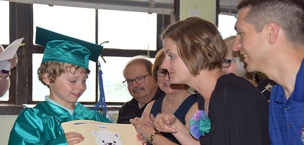 A little graduate in green cap and gown shows his certificate to his Mom and Dad during the Universal Pre-K graduation at the Cub Care campus.