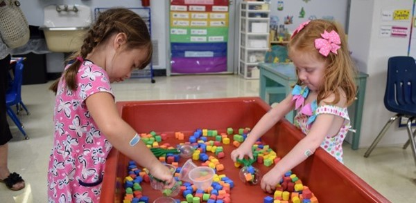 Two girls play together sorting colored shapes in a big red bin during Vestal's Universal Pre-Kindergarten orientation at the Jewish Community Center campus on September 4, 2018