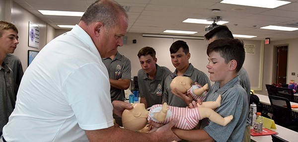 Vestal Middle School's School Resource Officer instructs a Youth Police Academy cadet how to perform C P R  on an infant dummy during a session at Vestal High School on July 25, 2019.