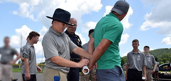 A Youth Police Academy cadet cuffs the Vestal High School Resource Officer during a traffic stop scenario on July 24, 2019, taking place behind the high school.