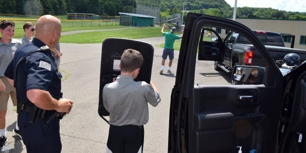A Vestal Police Lieutenant directs a Vestal High School Youth Police Academy cadet holding a S W A T  shield during a traffic stop scenario.