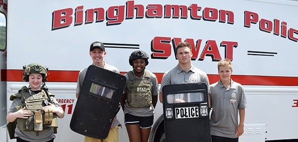 Five Vestal High School Youth Police Academy cadets, two girls and three boys, pose for a photo in front of the Binghamton S W A T  truck wearing police vests, S W A T helmets and holding shields.