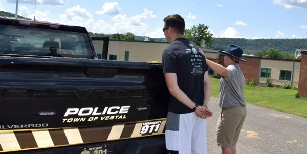 A Vestal Police Officer acting as a culprit, stands behind a Town of Vestal Police truck while a Youth Police Academy cadet restrains him during the traffic stop scenarios on July 24, 2019.