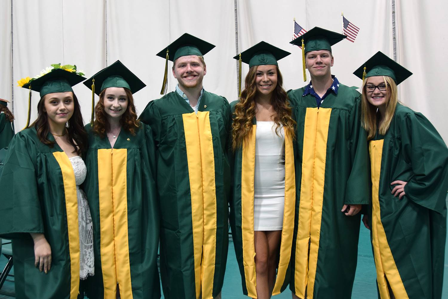 Six friends get ready behind the white curtain in the Binghamton University Events Center before the