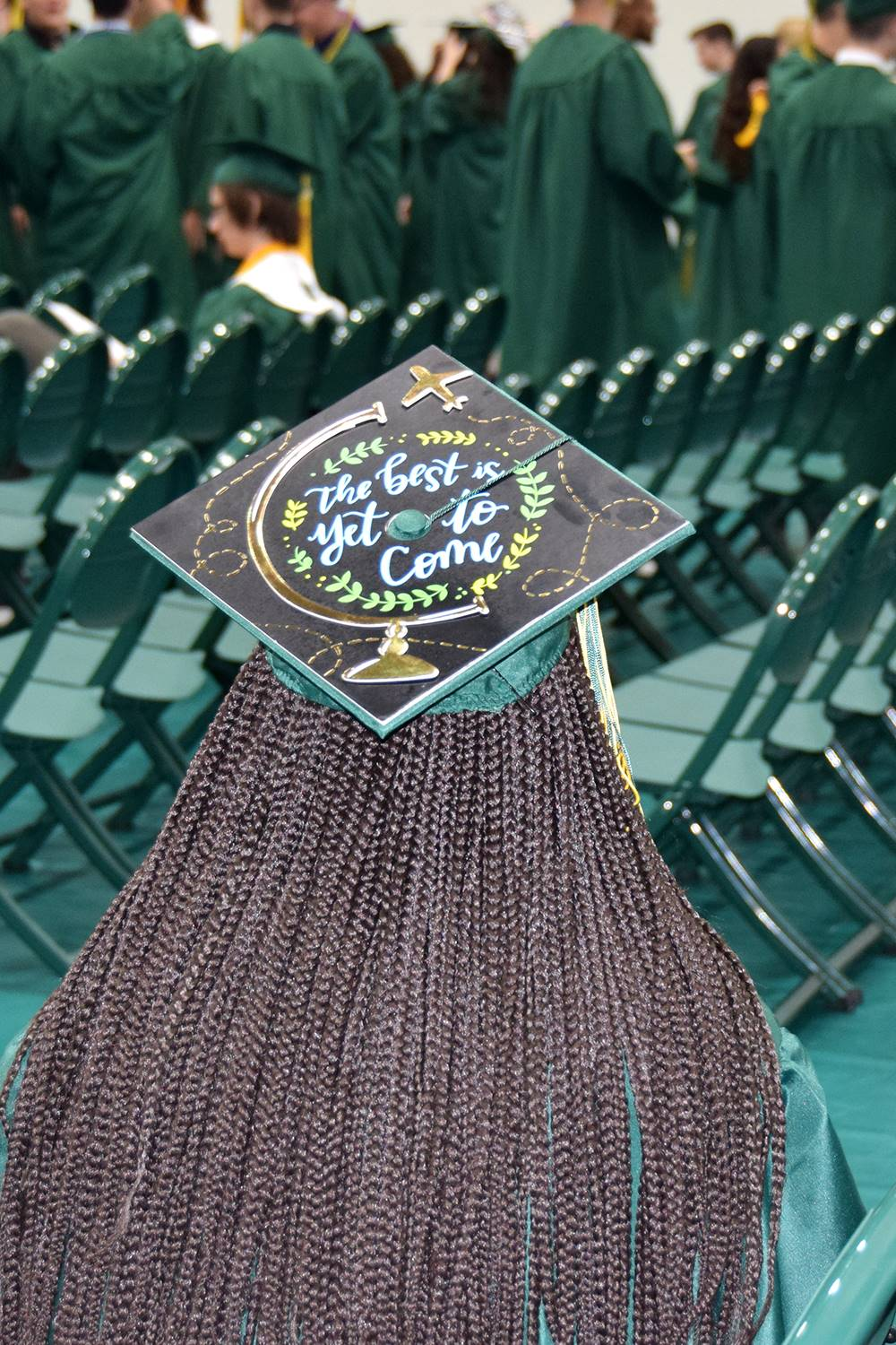 A Vestal High School senior with long braids sits as she waits for Graduation with a decorated morta
