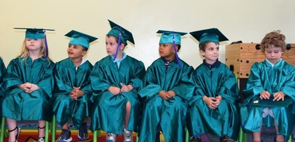 A row of tiny students in green caps and gowns are seated at the front of the room at the beginning of the Universal Pre-Kindergarten graduation at the Cub Care campus on June 20, 2019.