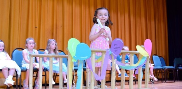 A girl in pink dress with daisies clutches a white scrolled-up paper as she crosses a little wooden bridge decorated with paper balloons during the Universal Pre-Kindergarten Graduation ceremony at the Jewish Community Center campus.