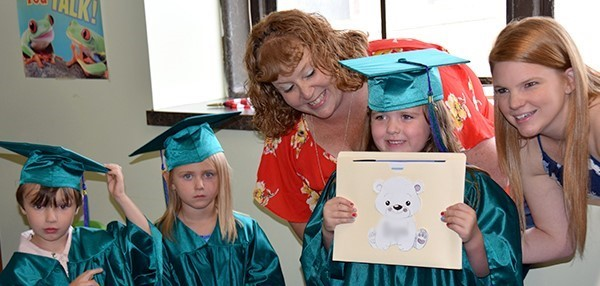 A girl in green cap and gown proudly holds a diploma up to her chin during the Universal Pre-Kindergarten graduation at the Cub Care campus on June 20, 2019.