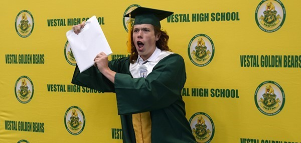 A Vestal High School graduate holds his diploma as he poses for the official photo in front of the green and gold wall during graduation in the Binghamton University Events Center on June 29, 2019.