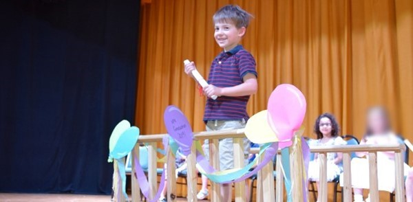 A boy crossing a bridge holds his Universal Pre-Kindergarten diploma during one of the Graduation ceremonies at the Jewish Community Center campus.