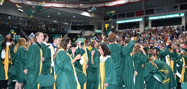 Vestal High School students in green caps and gowns toss their caps in the air at the end of Graduation on June 29,2019.