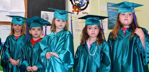 Five small students in the Universal Pre-Kindergarten program at the Cub Care campus stand side by side in green satin caps and gowns just before the graduation ceremony on June 20, 2019.