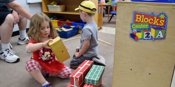A pre-kindergarten student in red dress with red and-white checked leggings stacks cardboard blocks in her classroom at the Jewish Community Center campus during orientation on September 3, 2019. A boy in a yellow baseball hat is playing behind her.