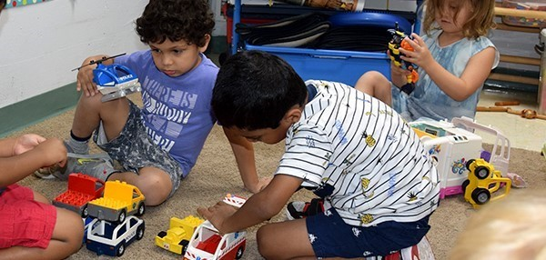 Two boys play trucks on a play mat while another girl plays behind them during Universal Pre-Kindergarten orientation at the Jewish Community Center campus on September 3, 2019.