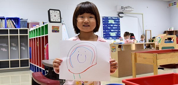A girl holds up a self-portrait of herself she drew during Universal Pre-Kindergarten orientation at the Jewish Community Center on September 3, 2019.