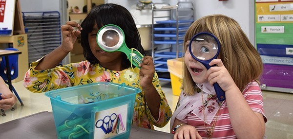 Two girls hold toy magnifying glasses up to one eye as they get to know each other during Universal Pre-Kindergarten orientation at the Jewish Community Center campus on September 3, 2019.