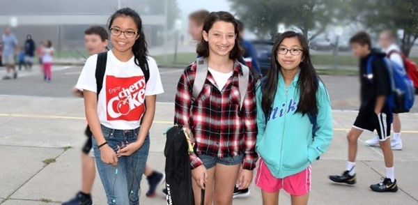 Three Vestal Middle School girls walk up the sidewalk after getting off the bus on the first day of school, September 5, 2019.