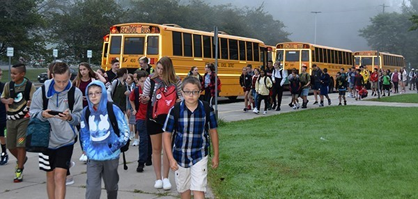 Vestal Middle School students flow up the sidewalk in a steady stream after getting off their school buses on the first day of school, September 5, 2019.