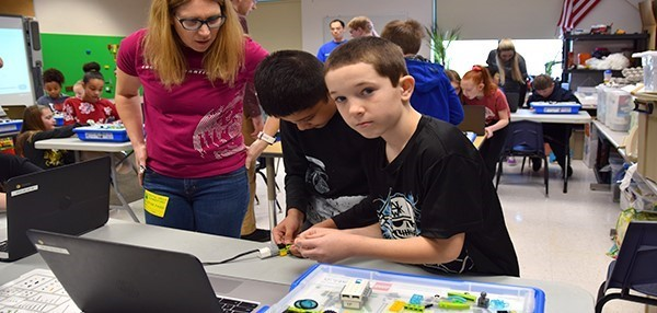 A Lockheed Martin volunteer assists two Vestal Hills Elementary fourth-grade boys who are assembling their L E G O  robot in the Maker Space room on January 24, 2020.