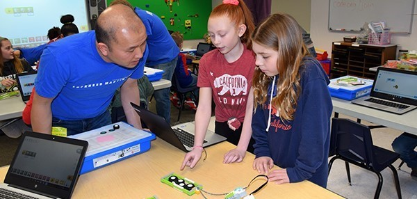 A Lockheed Martin volunteer helps two Vestal Hills Elementary fourth-grade girls figure out what is keeping their L E G O  robot from pulling the sled. One girl realizes that the element of friction is hampering the device.