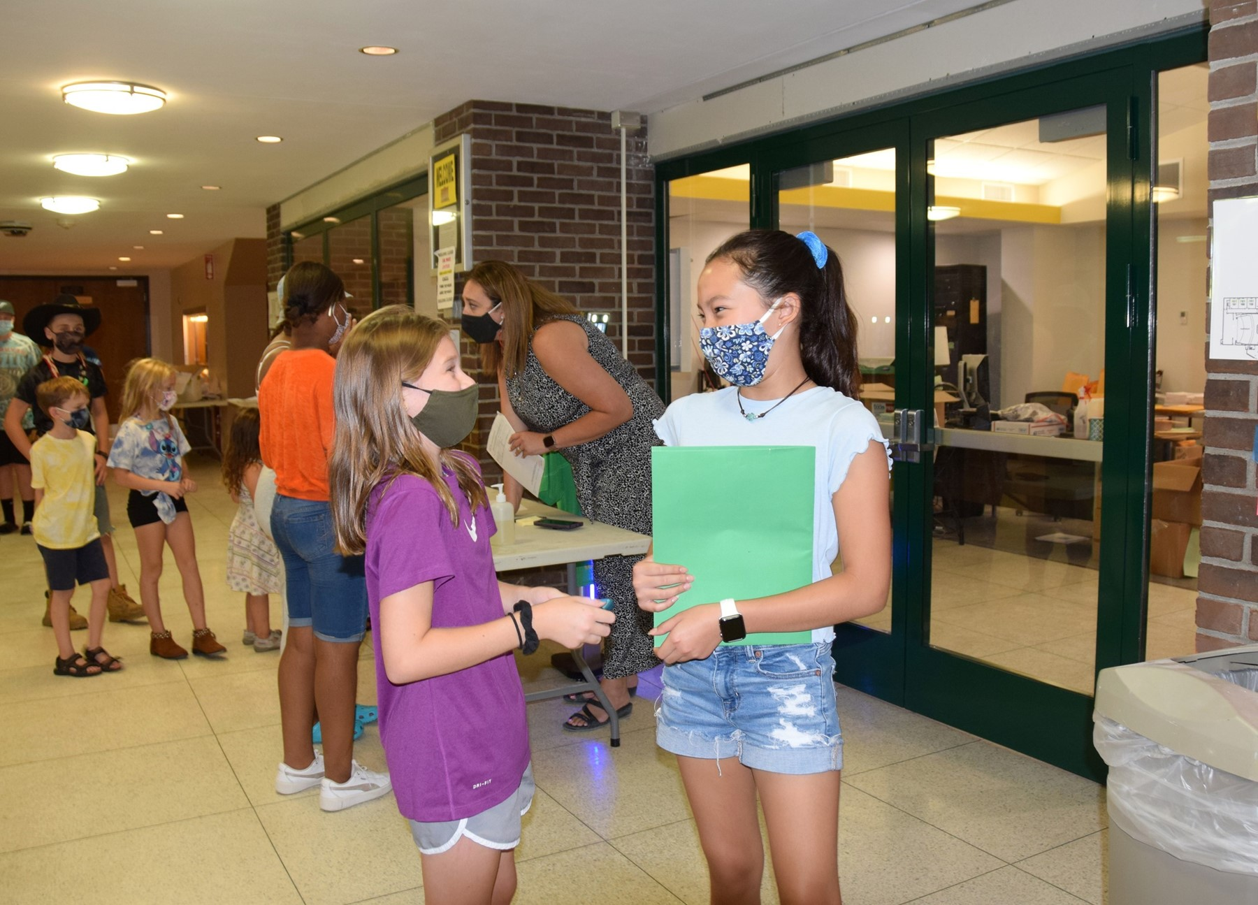 Two Vestal Middle School students, both girls, catch up during building-access time two days before school starts.