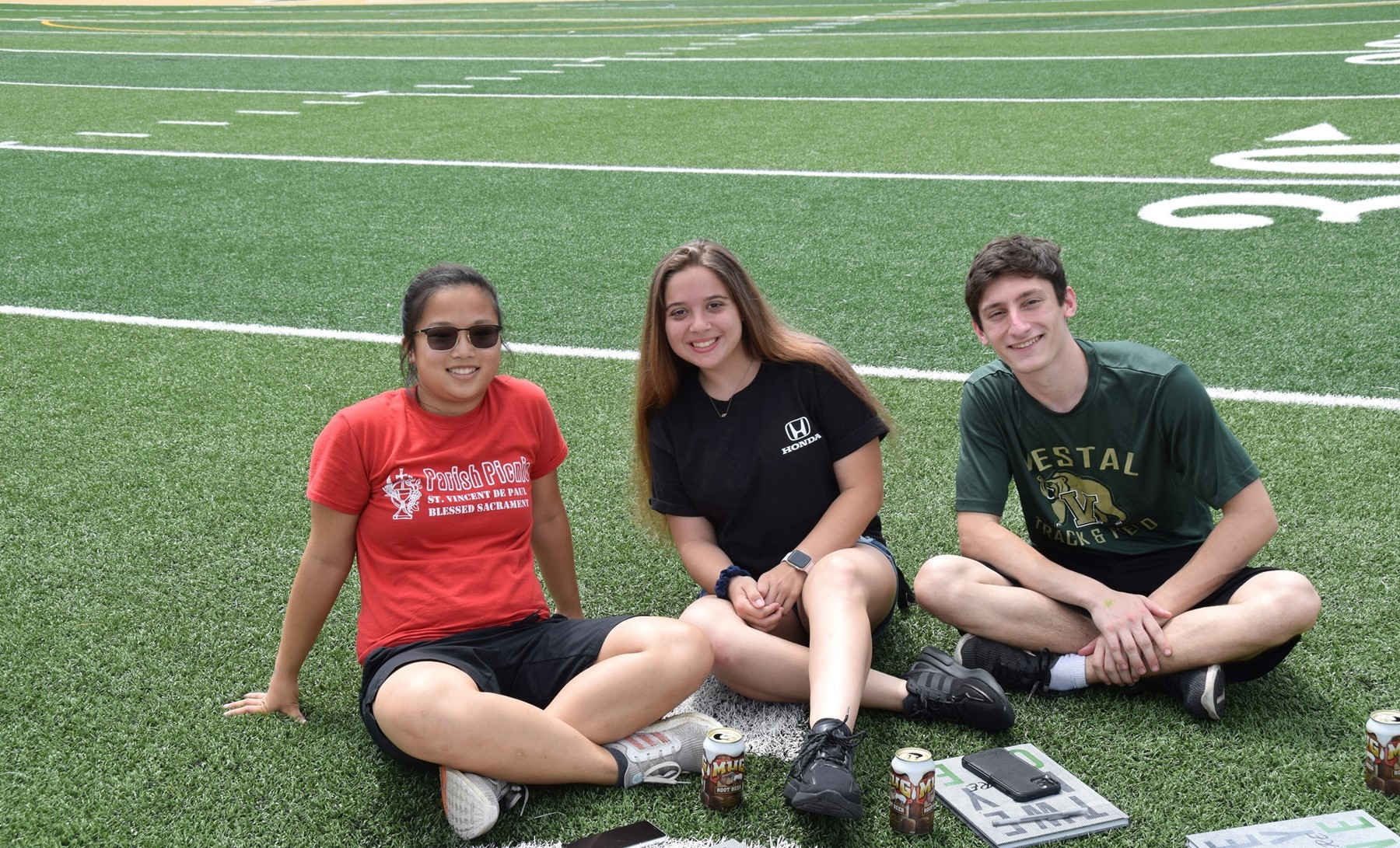 Three Vestal High School seniors sit on the grass in Hoover Stadium as they enjoy their 2021 Prom Promise Picnic on June 9, 2021.