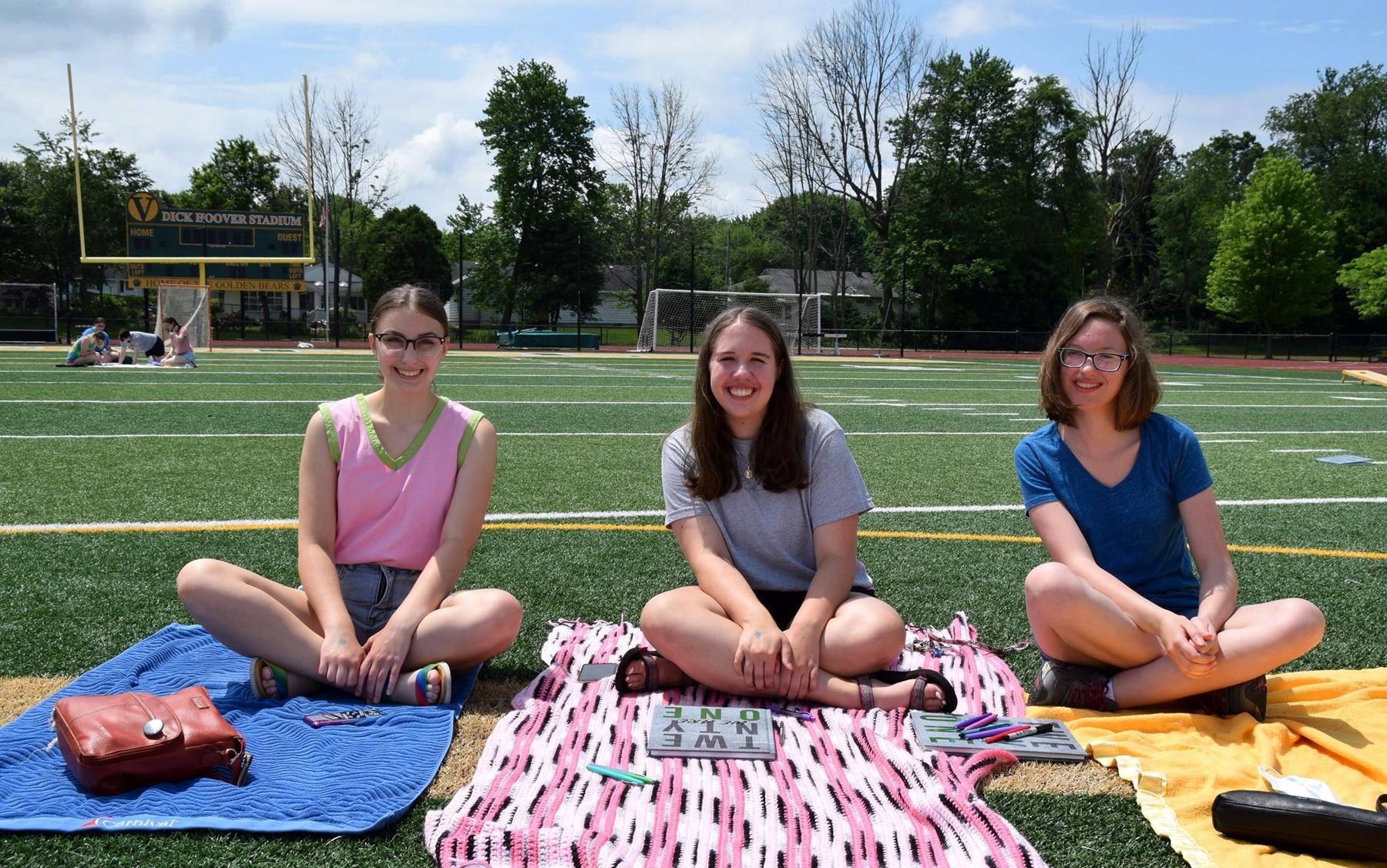 Three Vestal High School senior girls sit smiling on blankets in Hoover Stadium during their Prom Promise Picnic on June 9, 2021.
