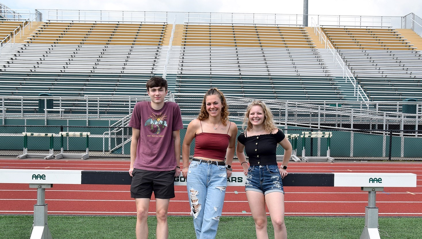 Three Vestal High School seniors, a guy and two girls, lean against a cross-country obstacle in Hoover Stadium during their Prom Promise Picnic.