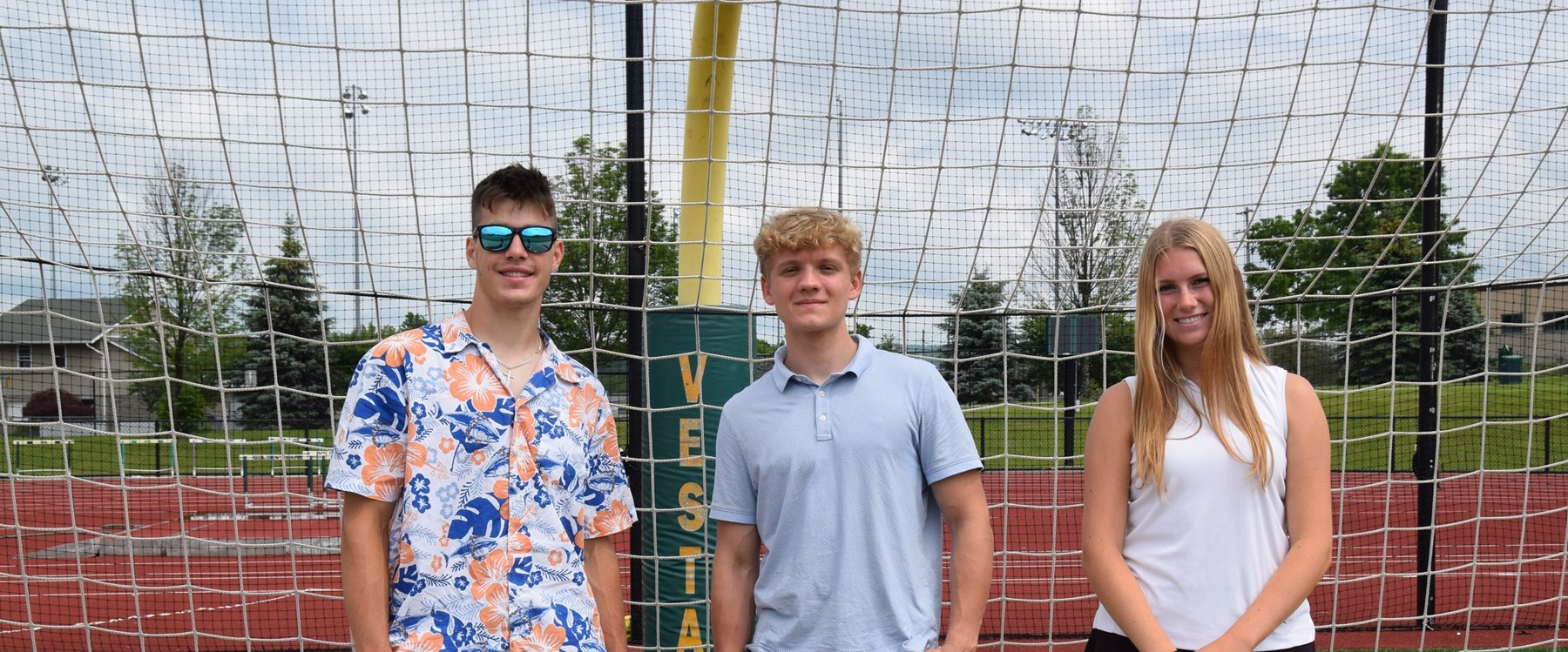 Three Vestal High School seniors stand in front of the goal net on the field in Hoover Stadium during their 2021 Prom Promise Picnic on June 9, 2021.
