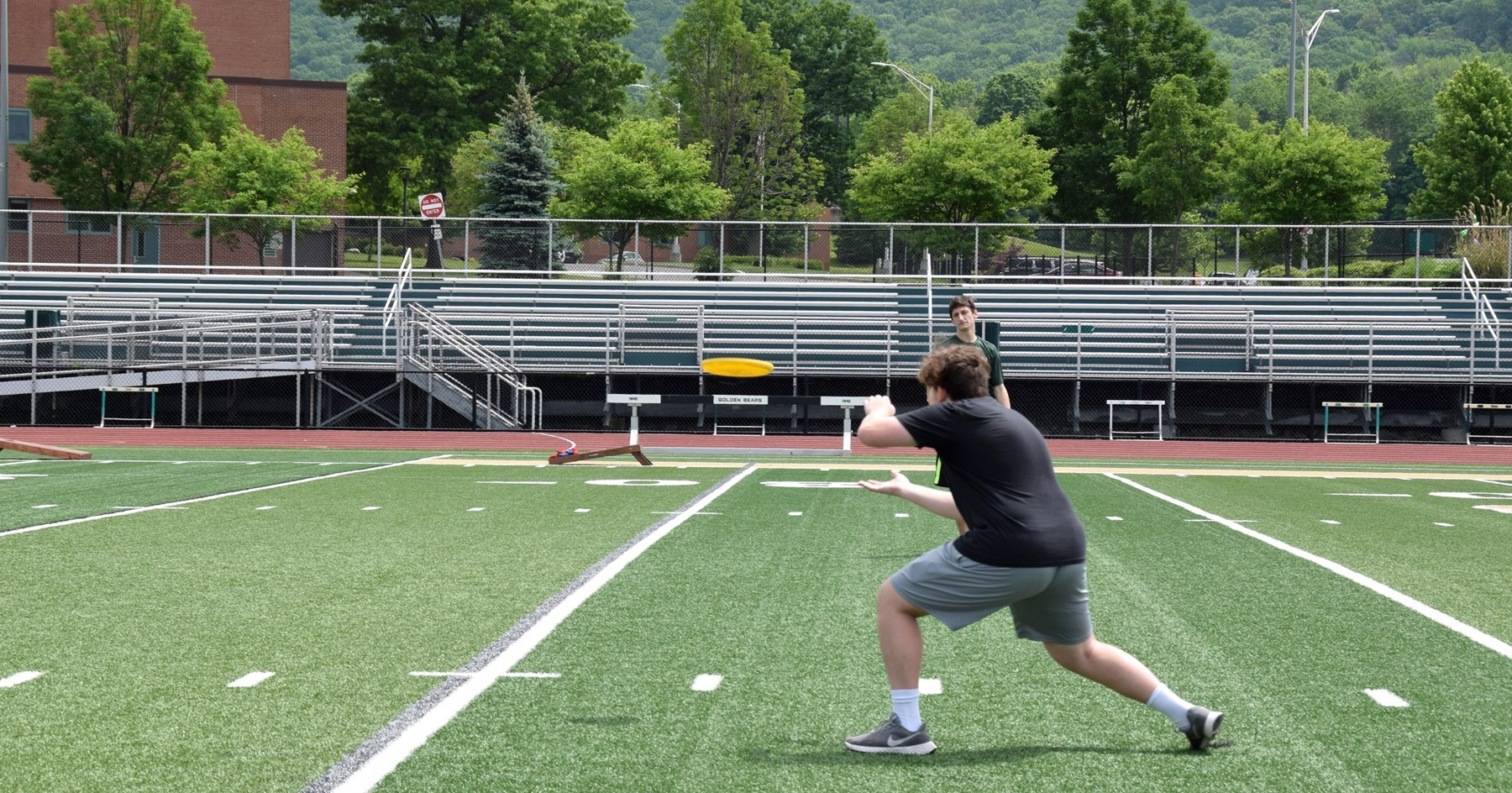 A vestal High School senior is about to catch a yellow frisbie during a casual game on the field of Hoover Stadium during the Prom Promise Picnic.