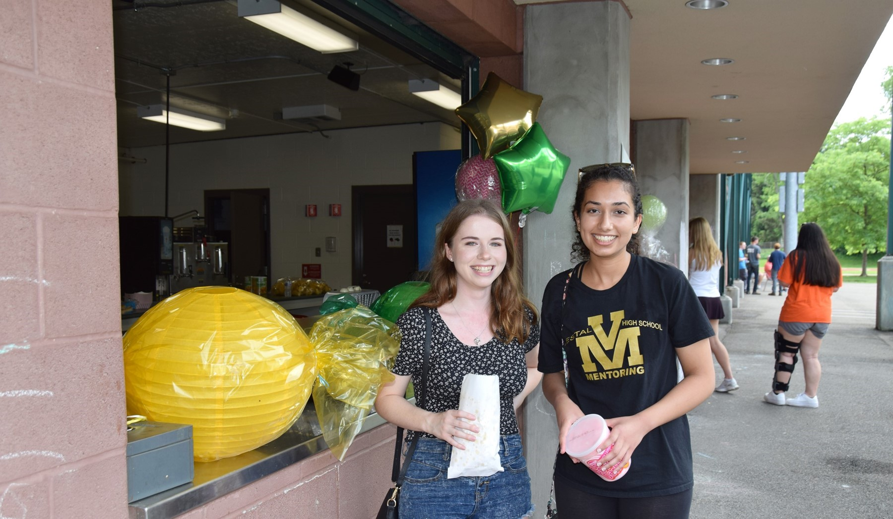 Two Vestal High School senior girls leave the concession stand in Hoover Stadium with cotton candy and popcorn.