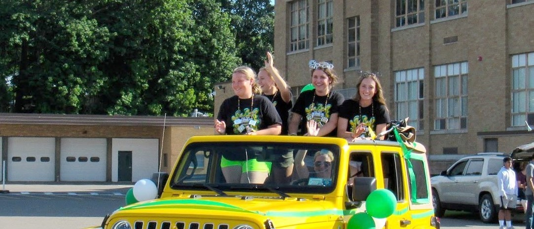 Senior girls in a yellow jeep decorated with green streamers for the Senior Car Parade proceed around the back of the Central Junior building on their way to Vestal High School on June 4, 2021.