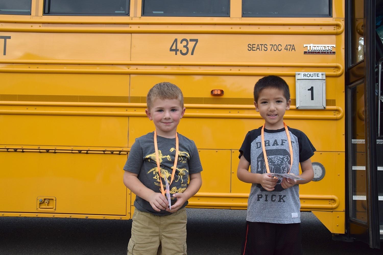 Two Kindergarten boys stand in front of a Vestal School Bus.
