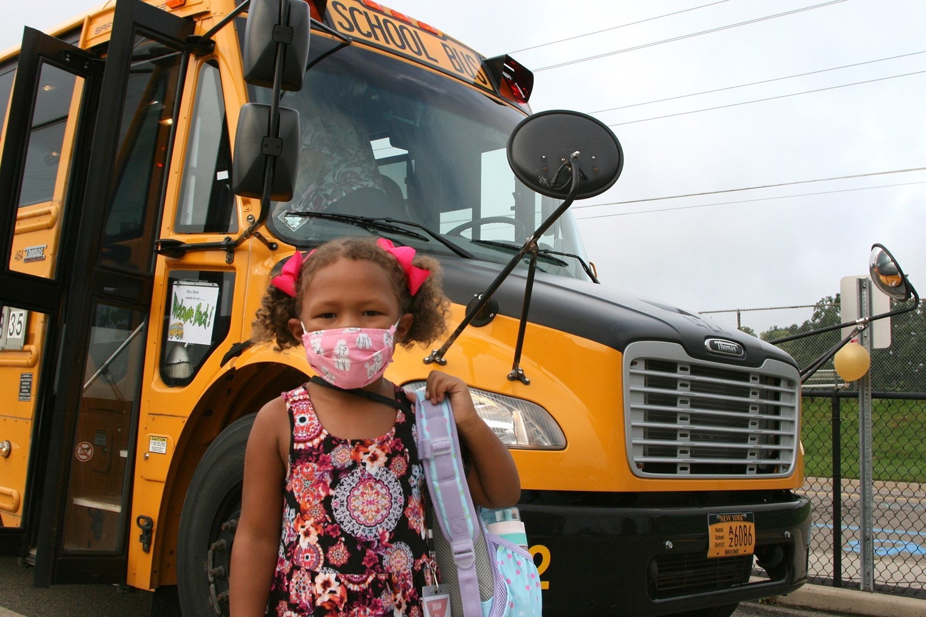 A Clayton Avenue Kindergarten student with pink bows on her pig tails stands in front of the school bus on the first day of school.