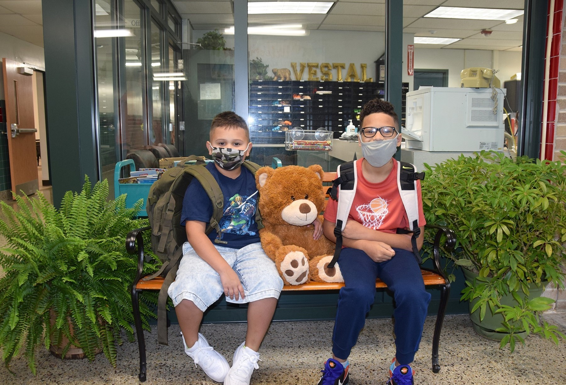 Two boys sit on either side of a stuffed brown bear on the bench in the Glenwood Elementary School lobby on the first day of school 2021.