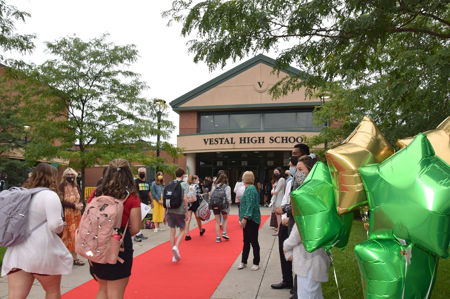 Students travel up a red carpet flanked by green and gold balloons and waving teachers as they arrive for the first day of school on September 9, 2021.